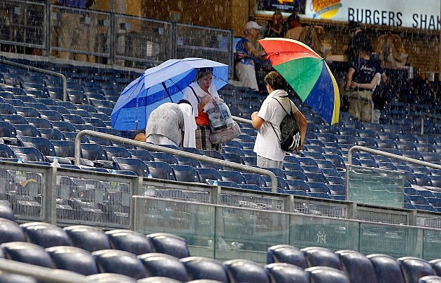 NEW YORK, NY - JULY 18: Fans pack up to leave after the game between the New York Yankees and the Toronto Blue Jays was called in the seventh inning due to rain against the at Yankee Stadium on July 18, 2012 in the Bronx borough of New York City. (Photo by Jim McIsaac/Getty Images)