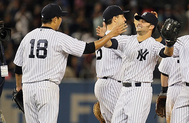 NEW YORK, NY - AUGUST 14: Hiroki Kuroda #18 of the New York Yankees celebrates with Nick Swisher #33 after pitching a complete game shutout against the Texas Rangers at Yankee Stadium on August 14, 2012 in the Bronx borough of New York City. Yankees defeated the Rangers 3-0. (Photo by Mike Stobe/Getty Images)