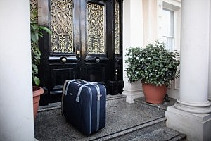 suitcase-in-front-of-doorstep-by-Dan-Kit