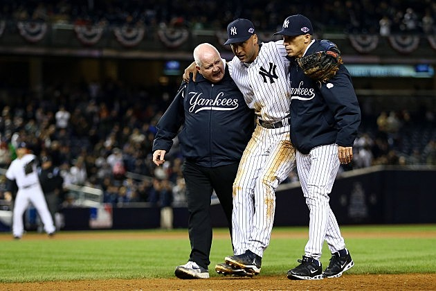 NEW YORK, NY - OCTOBER 13: Derek Jeter #2 of the New York Yankees is carried off of the field by trainer Steve Donohue (L) and manager Joe Girardi after Jeter injured his leg in the top of the 12th inning against the Detroit Tigers during Game One of the American League Championship Series at Yankee Stadium on October 13, 2012 in the Bronx borough of New York City, New York. (Photo by Al Bello/Getty Images)