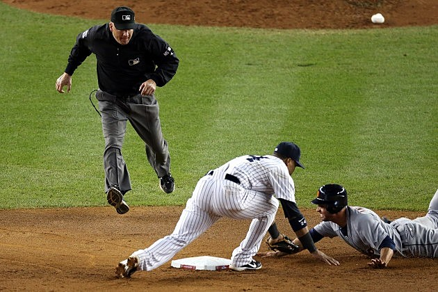 NEW YORK, NY - OCTOBER 14: Umpire Jeff Nelson calls Omar Infante #4 of the Detroit Tigers safe as he dove back into second base against Robinson Cano #24 of the New York Yankees in the top of the eighth inning during Game Two of the American League Championship Series at Yankee Stadium on October 14, 2012 in the Bronx borough of New York City. (Photo by Bruce Bennett/Getty Images)