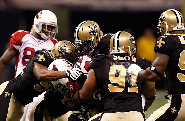 NEW ORLEANS - JANUARY 16: Jonathan Vilma #51 (L) and Will Smith #91 of the New Orleans Saints with an assits from teammates tackle Tim Hightower #34 of the Arizona Cardinals during the NFC Divisional Playoff Game at Louisana Superdome on January 16, 2010 in New Orleans, Louisiana. The Saints won 45-14. (Photo by Chris Graythen/Getty Images)