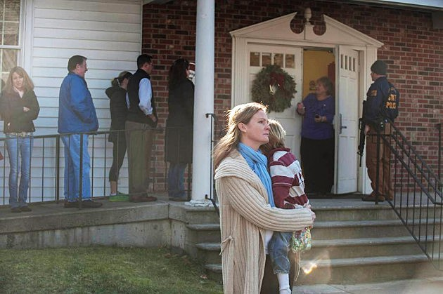 NEWTOWN, CT - DECEMBER 14: A woman holds a child as people line up to enter the Newtown Methodist Church near the the scene of an elementary school shooting on December 14, 2012 in Newtown, Connecticut. According to reports, there are about 27 dead, 18 children, after a gunman opened fire in at the Sandy Hook Elementary School. The shooter was also killed. (Photo by Douglas Healey/Getty Images)