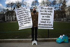 LONDON, ENGLAND - FEBRUARY 05: Born again Christian Carl Hamblin holds banners quoting the Bible as he stands in Parliament Square on February 5, 2013 in London, England. Later Parliament will hold a vote on whether to allow homosexual couples to marry. (Photo by Peter Macdiarmid/Getty Images)