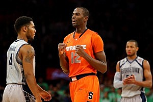 NEW YORK, NY - MARCH 15: Baye Keita #12 of the Syracuse Orange reacts against D'Vauntes Smith-Rivera #4 and Jabril Trawick (R) #55 of the Georgetown Hoyas in overtime during the semifinals of the Big East Men's Basketball Tournament at Madison Square Garden on March 15, 2013 in New York City. (Photo by Al Bello/Getty Images)