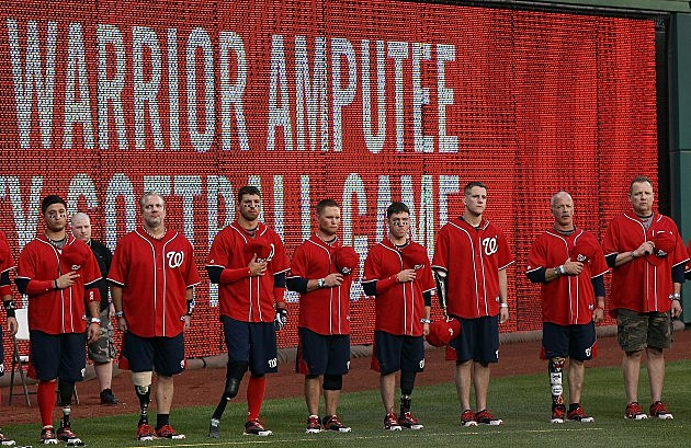 WASHINGTON, DC - APRIL 03: Members of the Washington Nationals Wounded Warrior softball team observe the national anthem before the start of the Wounded Warrior Amputee Celebrity Softball Classic at Nationals Park April 3, 2012 in Washington, DC. With a team comprised of veterans and active duty service members from across the United States who lost limbs while serving in Iraq or Afghanistan, members of the Washington Nationals Wounded Warrior softball team travel the country competing against able-bodied opponents. (Photo by Win McNamee/Getty Images)