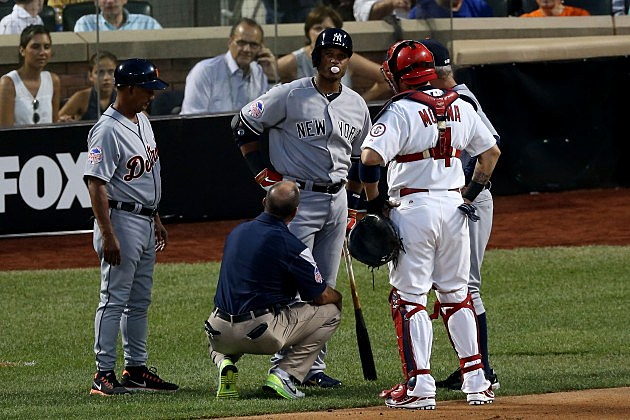NEW YORK, NY - JULY 16: American League All-Star Robinson Cano #24 of the New York Yankees is checked on after getting hit by a pitch as National League All-Star Yadier Molina #4 of the St. Louis Cardinals looks on during the 84th MLB All-Star Game on July 16, 2013 at Citi Field in the Flushing neighborhood of the Queens borough of New York City. (Photo by Bruce Bennett/Getty Images)
