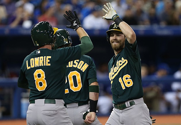TORONTO, CANADA - AUGUST 9: Josh Reddick #16 of the Oakland Athletics is congratulated by Jed Lowrie #8 and Josh Donaldson #20 after hitting a 3-run home run in the sixth inning during MLB game action against the Toronto Blue Jays on August 9, 2013 at Rogers Centre in Toronto, Ontario, Canada. (Photo by Tom Szczerbowski/Getty Images)