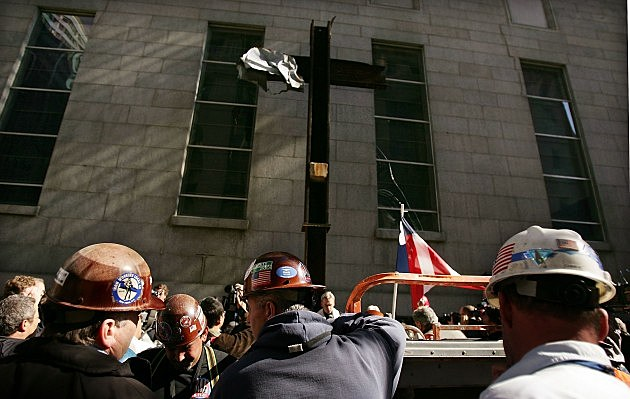 NEW YORK - OCTOBER 05:  During a brief religious service, construction workers stand beside the new temporary home for the steel beam in the shape of a cross that was left standing in the rubble of the World Trade Center five years ago October 5, 2006 to St. Peter's Church in New York City. The 20-foot-tall beam, which has became a symbol for family, recovery workers and construction workers, was discovered in the smoking ruins two weeks after the Sept. 11, 2001. It will stay on an exterior wall of nearby St. Peter's Church during construction at the trade center site.  (Photo by Spencer Platt/Getty Images)