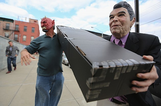 NEW YORK, NY - APRIL 13: Satirist Randy Credico (R) is dressed as U.S. President Ronald Reagan while carrying a mock coffin for former British Prime Minister Margaret Thatcher with a man dressed as Satan at an 'Irish wake' for Thatcher at Rocky Sullivan's Irish bar on April 13, 2013 in the Brooklyn borough of New York City. The celebration of Thatcher's death was held by activists in response to her policies and governance of Northern Ireland in the 1980s. (Photo by Mario Tama/Getty Images)