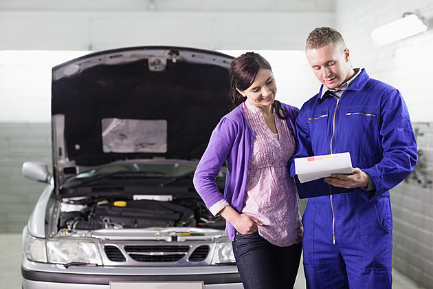 Mechanic showing a paper in a clipboard to a woman